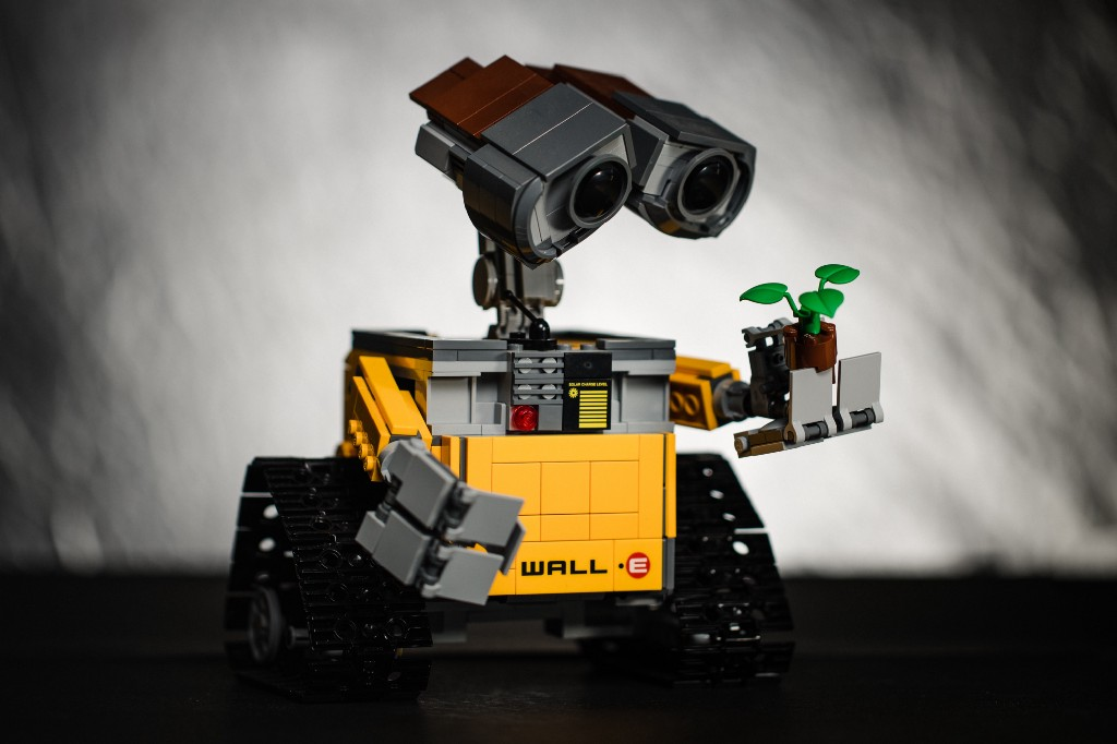 A robot lego toy holding a lego flower