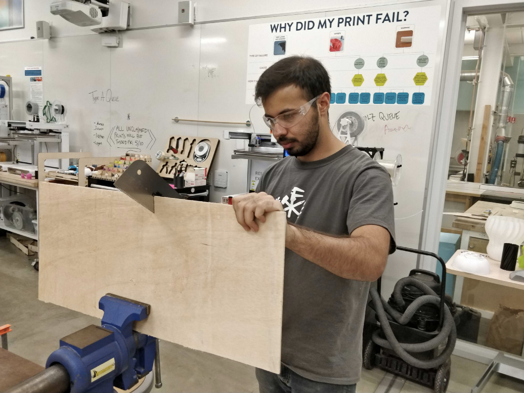 Shreyas works in a sort of makerspace, cutting a wood-like material in half with a saw.