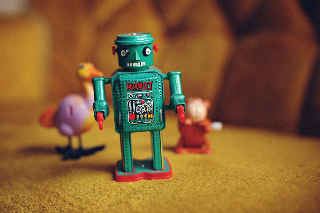 Green toy robot on the couch with other toys