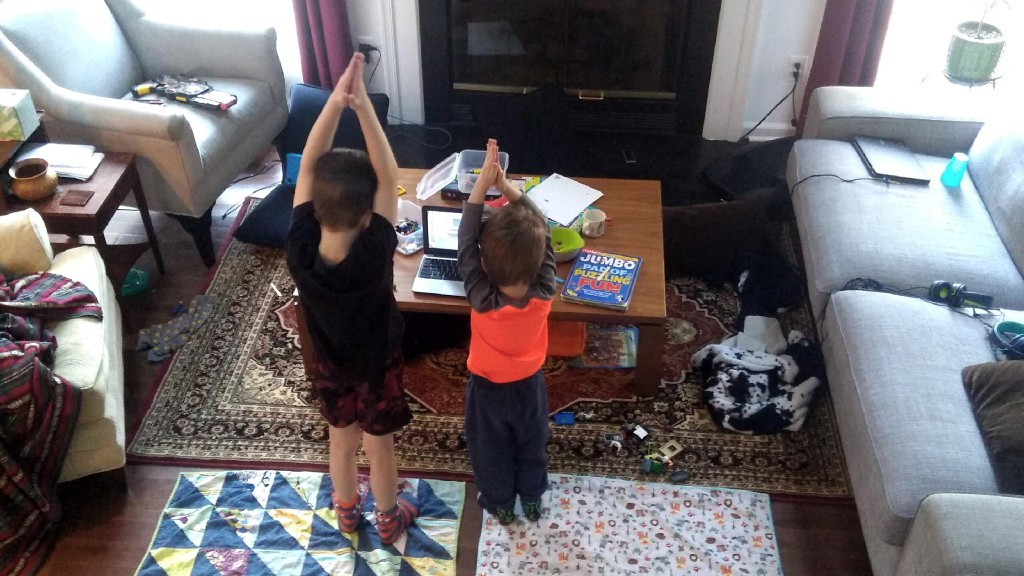 Two kids doing yoga in a messy living room.