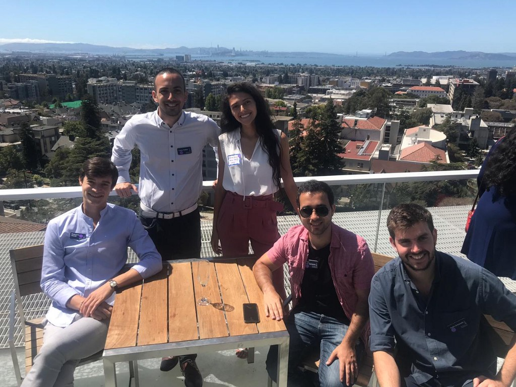 A group of young adults poses for a photo with a view of Berkeley campus.