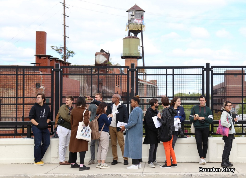 Maurice Cox, center, pointing, leads a group of Cornell University students on a tour of Detroit. Photo by Brandon Choy.