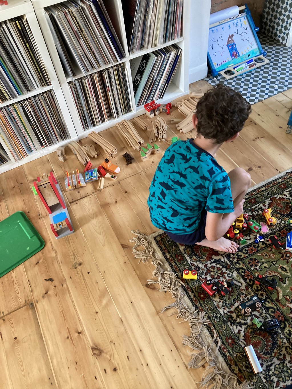 A young boy sorts out his train track and cars, methodically