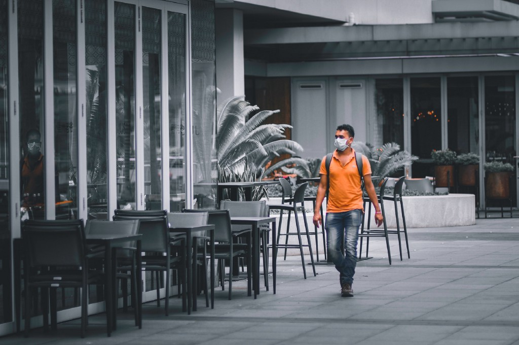 Man in face mask walks down empty walkway near a cafe