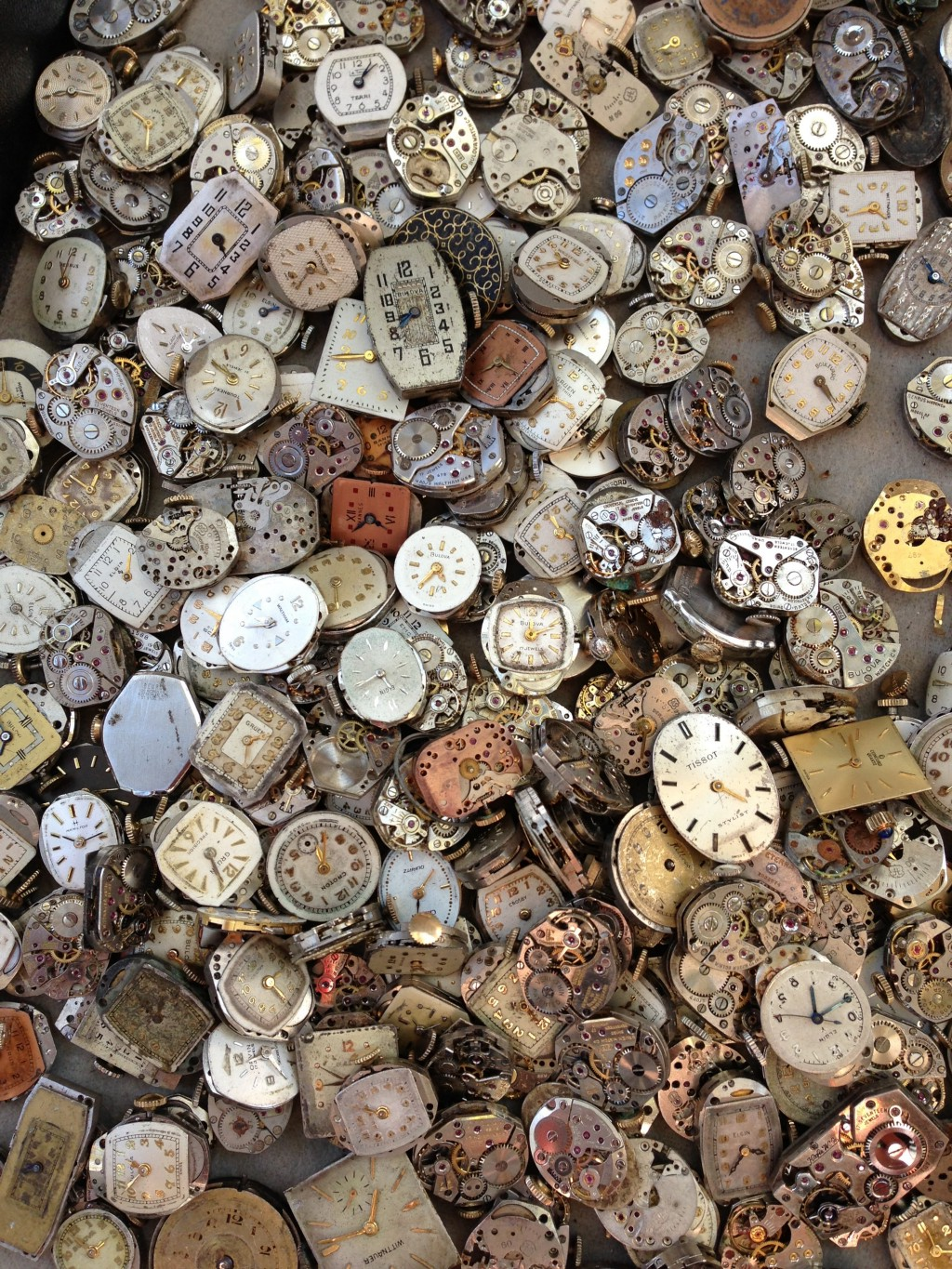 A handful of old and decrepit wrist watches.