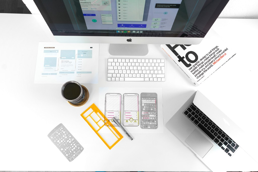 A typical designer's desk with wireframing tools, a laptop, and coffee.