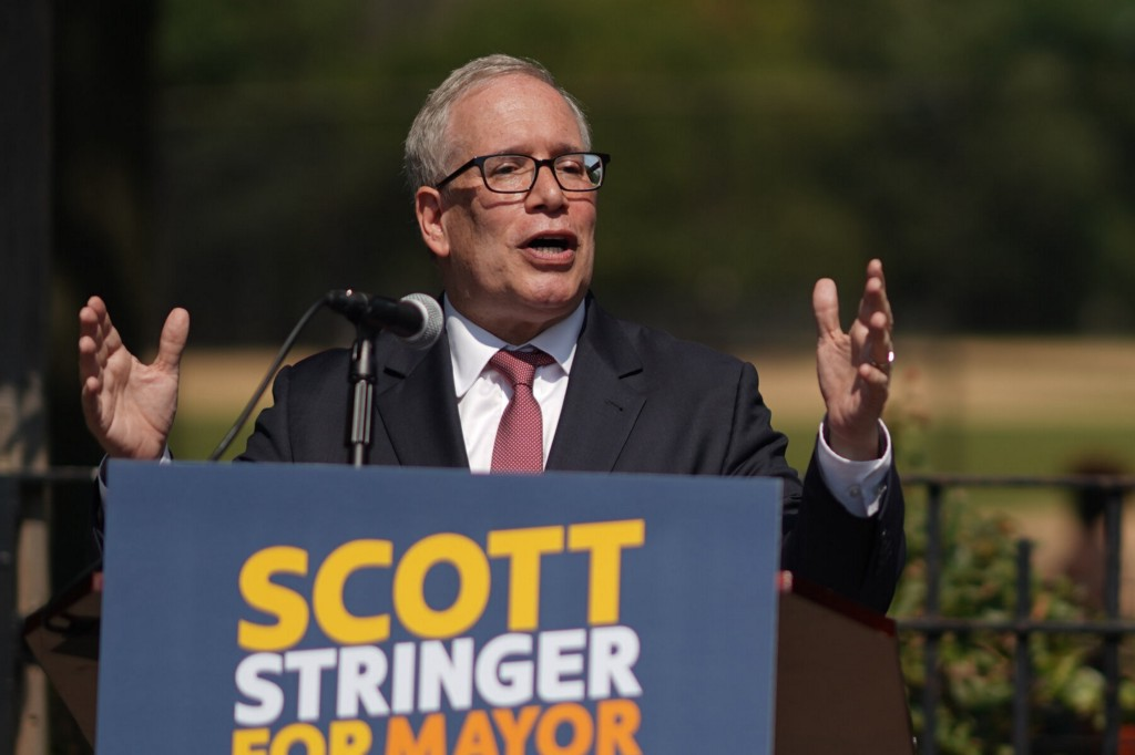 """Scott M. Stringer stands at podium in which a """"Scott Stringer for Mayor"""" is placed."""