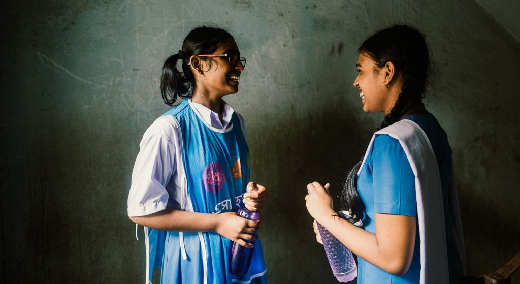 Two girls chat and smile in a hallway. Both hold water bottles and are wearing Splash vests.