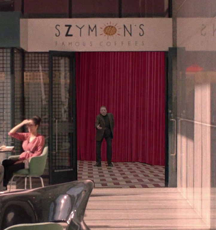 Mike/Phillip in the Red Room under the SZYMONS sign.