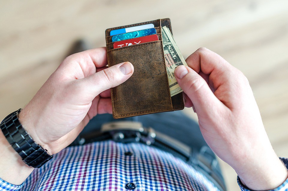 Man opening wallet to remove bills. Americans' financial health issues lead to many empty wallets.