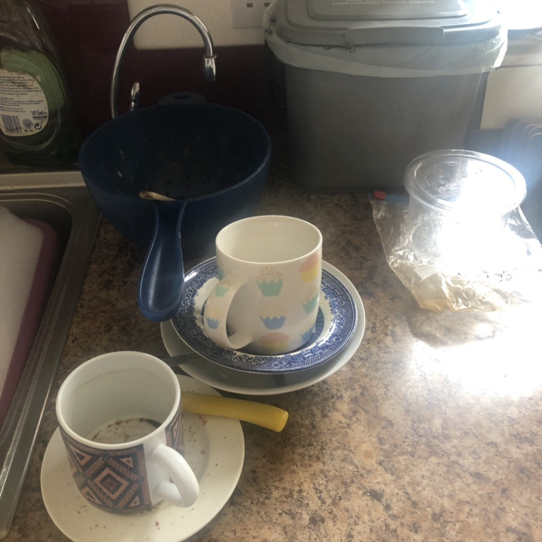 Pile of dirty dishes and cups next to basin