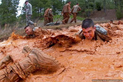 Recruits sloshing thru muddy water on their bellies