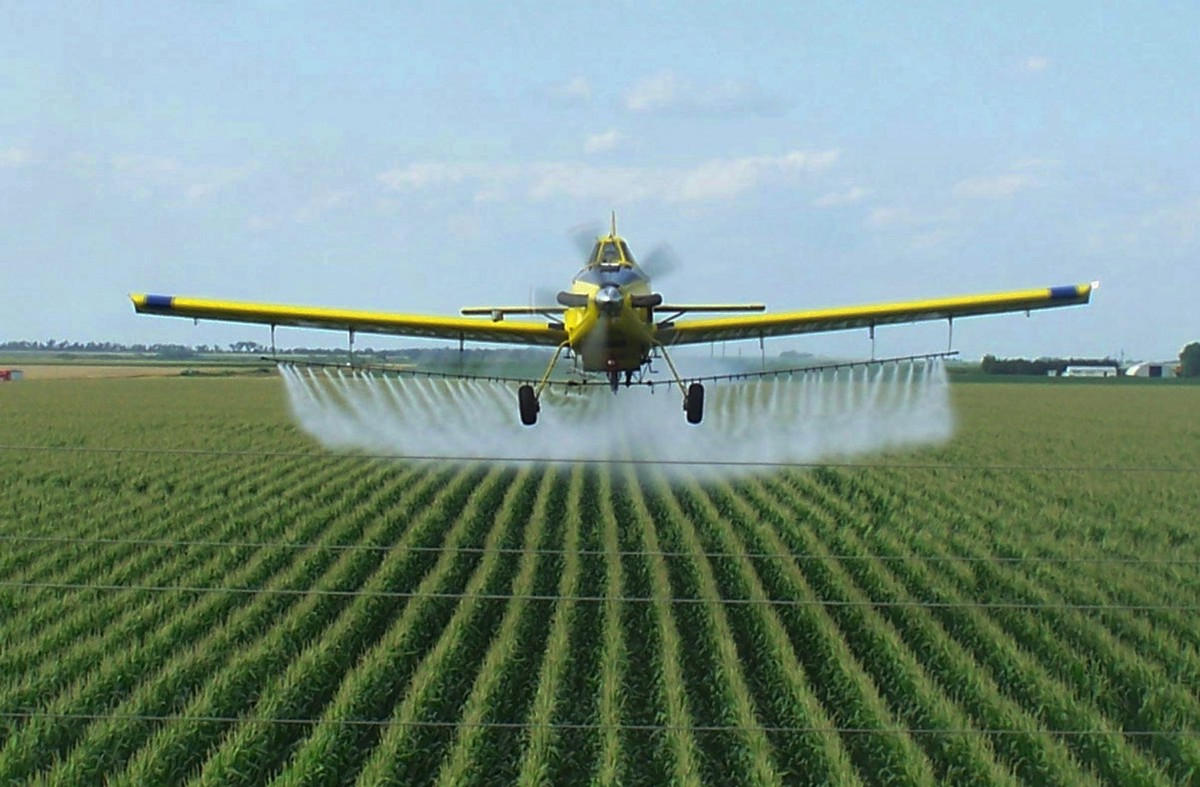 a crop dusting plane spraying the entire field