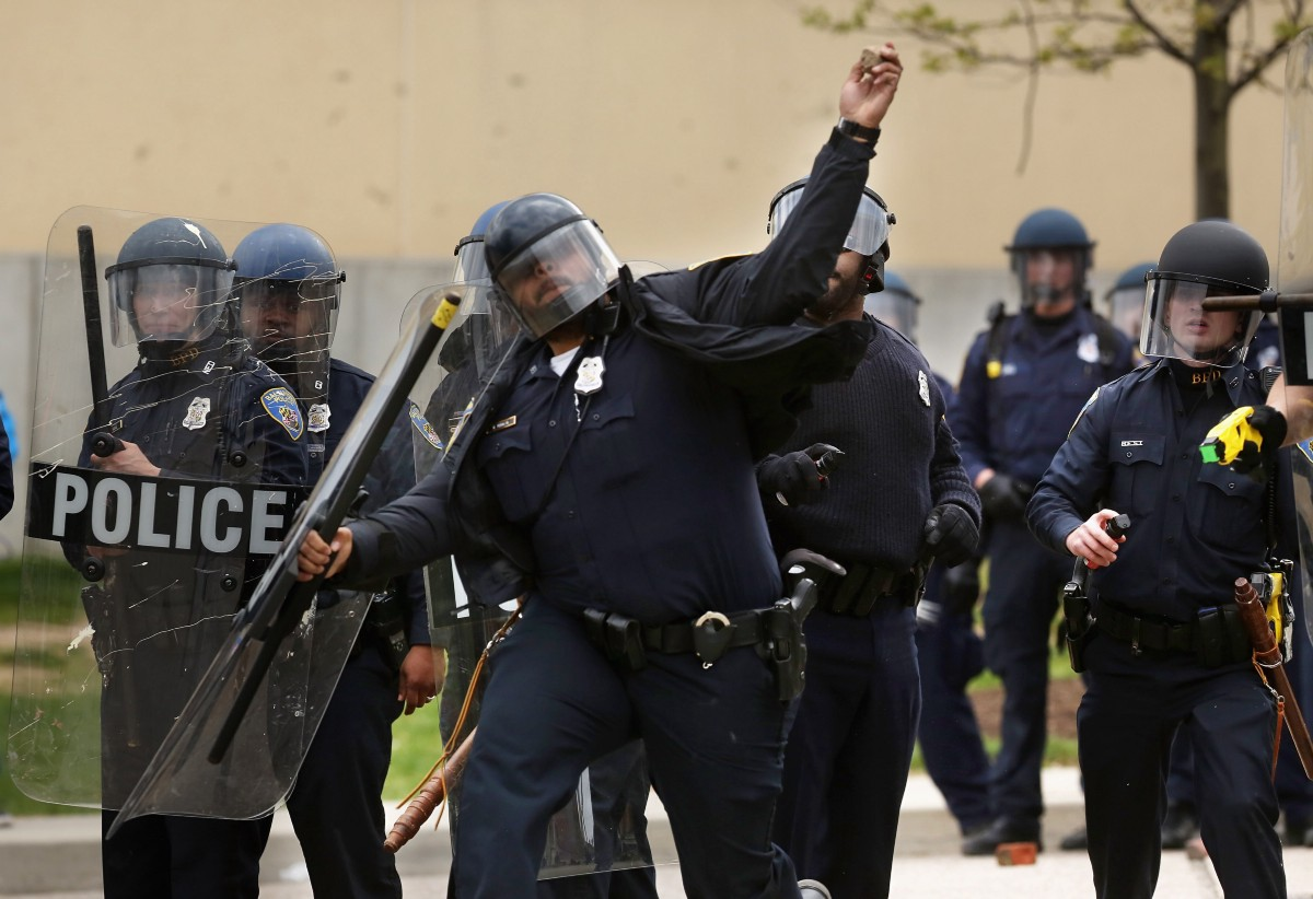 Baltimore police officers in riot gear push protestors back along - Left Young Person Hurls A Rock At Baltimore Police Officers Outside The Mondawmin Mall Following The Funeral Of Freddie Gray April 27 2015 In Baltimore