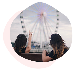 Two women with long hair pointing at a Ferris Wheel