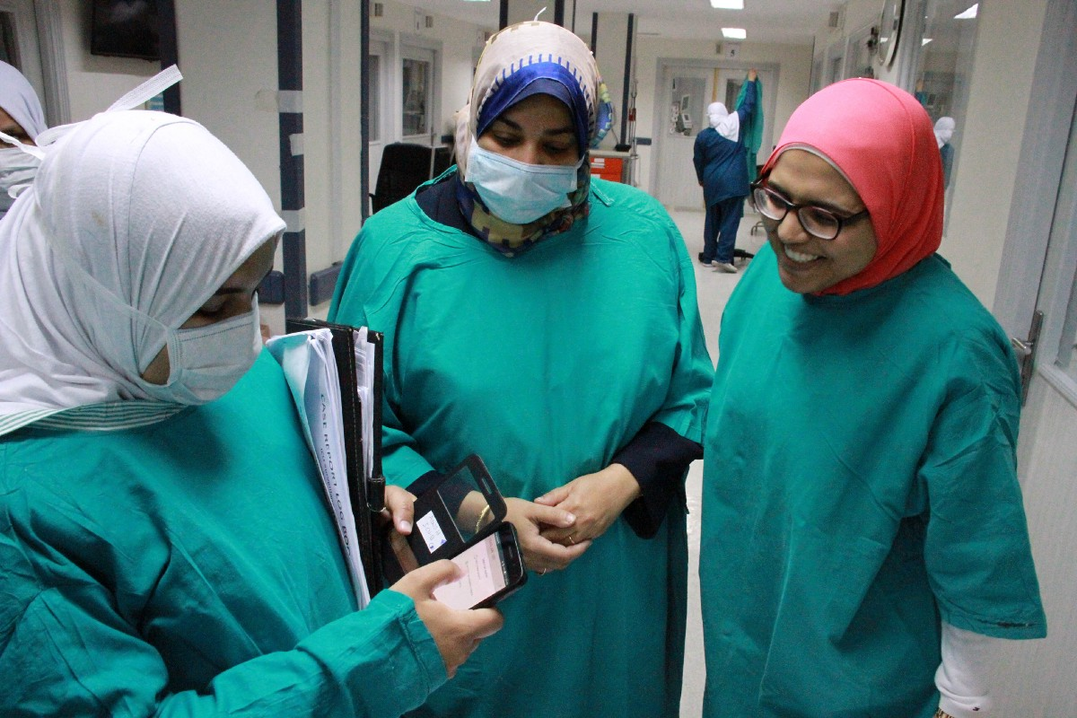 Nurses inside one of the hospital's ICUs confer with each other and a smartphone. / Jon Erb, USAID