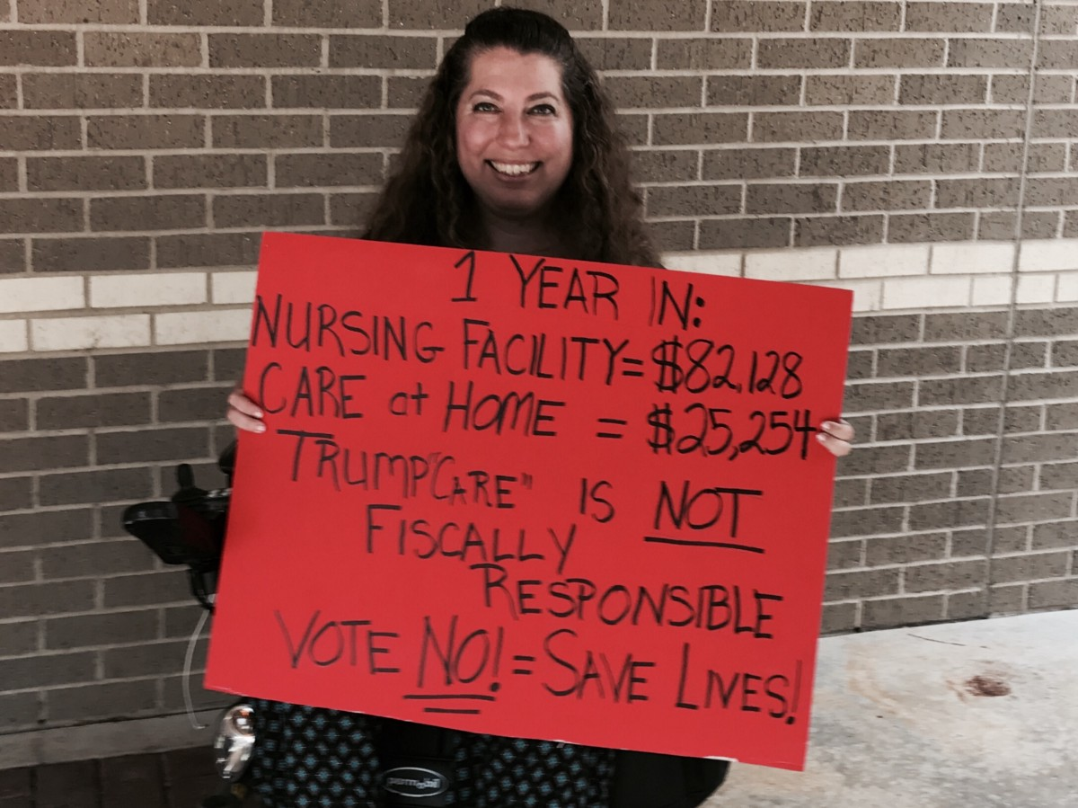 "Emily holds a sign from her power wheelchair that is almost as large as she is. The sign is made from red poster board and states: 1 Year In Nursing Facility = $82,128, Care at Home = $25,254, TrumpCare (the word ""care"" in quotes) is not fiscally responsible! Vote No! = Save Lives!"