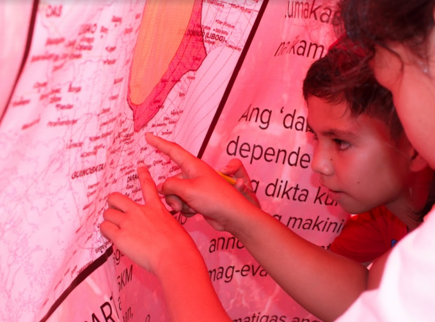 Children from Barangay Puro, a coastal area in Legazpi city, learning about disaster preparedness inside the Balangay game tent: a youth-targeted disaster information and Balangay promotional campaign. / Balangay