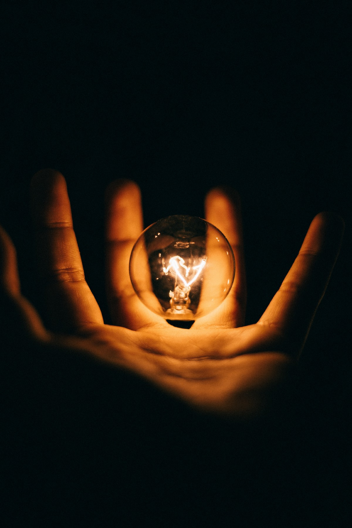 A lightbulb floating over the palm of a hand as it illuminates it.