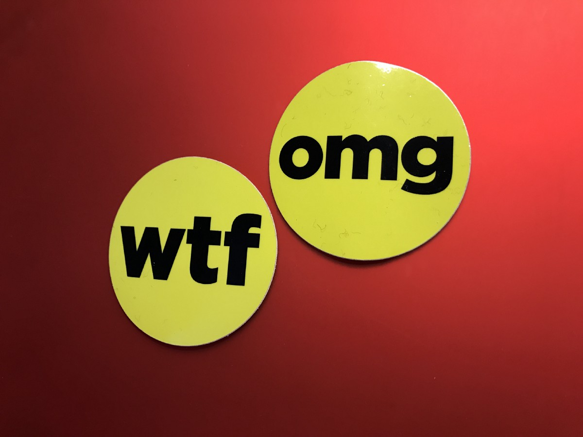 "At Buzzfeed corporate headquarters, wall art that states ""WTF"" and ""OMG"""