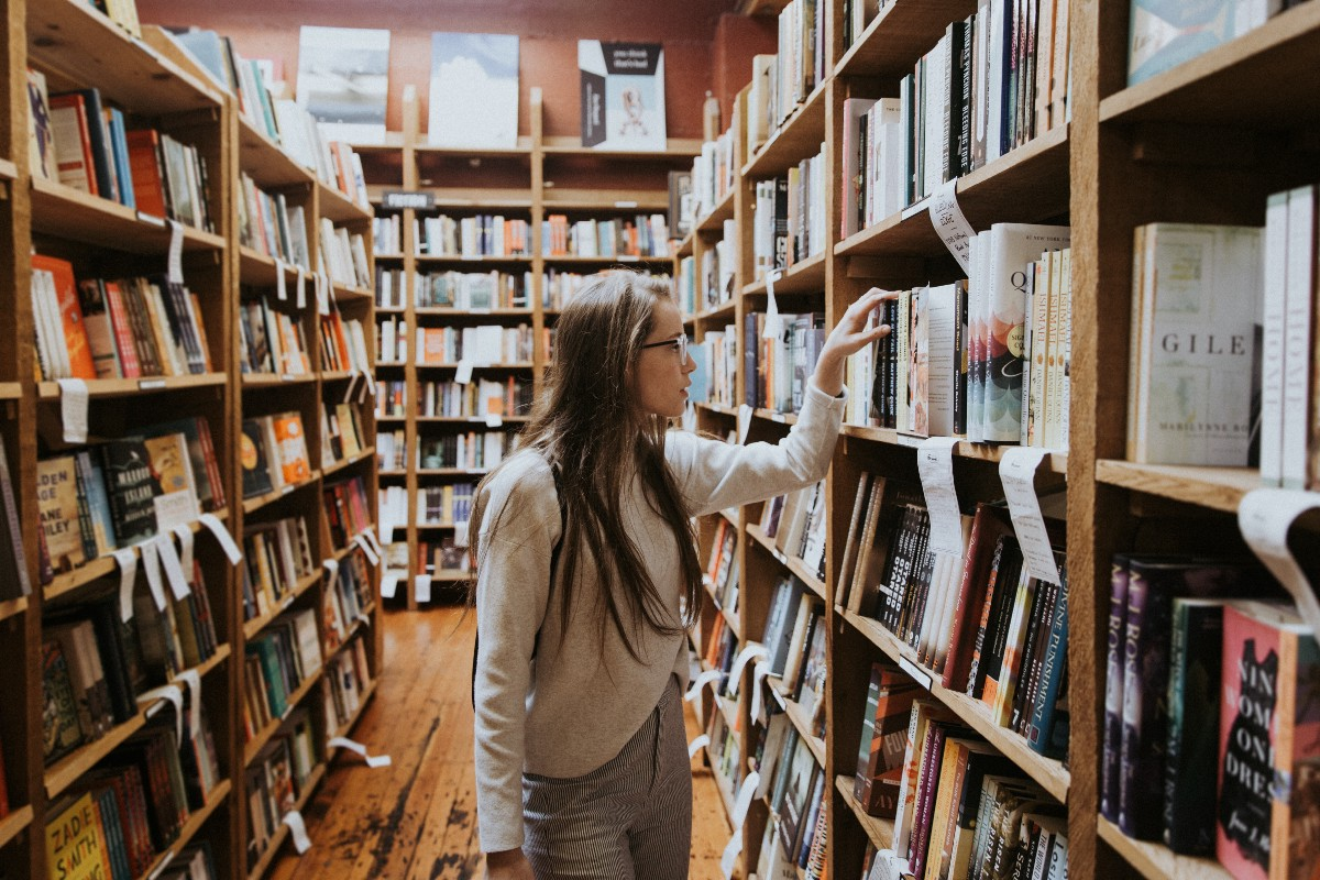 girl choosing a book from shelves