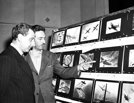 "Seversky and Walt Disney looking at boards for ""Victory Through Air Power."""