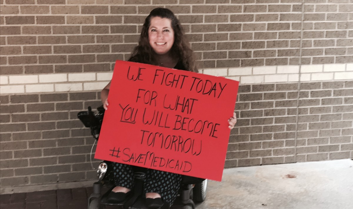 Emily holds a sign from her power wheelchair that is almost as large as she is. The sign is made from red poster board and states: We fight today for what you will become tomorrow. Hashtag Save Medicaid.