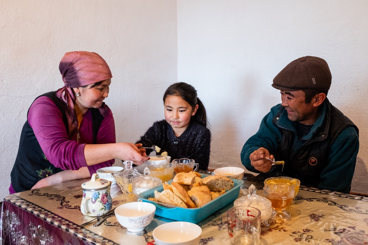 Ryskulbek's family having afternoon tea with honey. Photo: WFP/Danil Usmanov