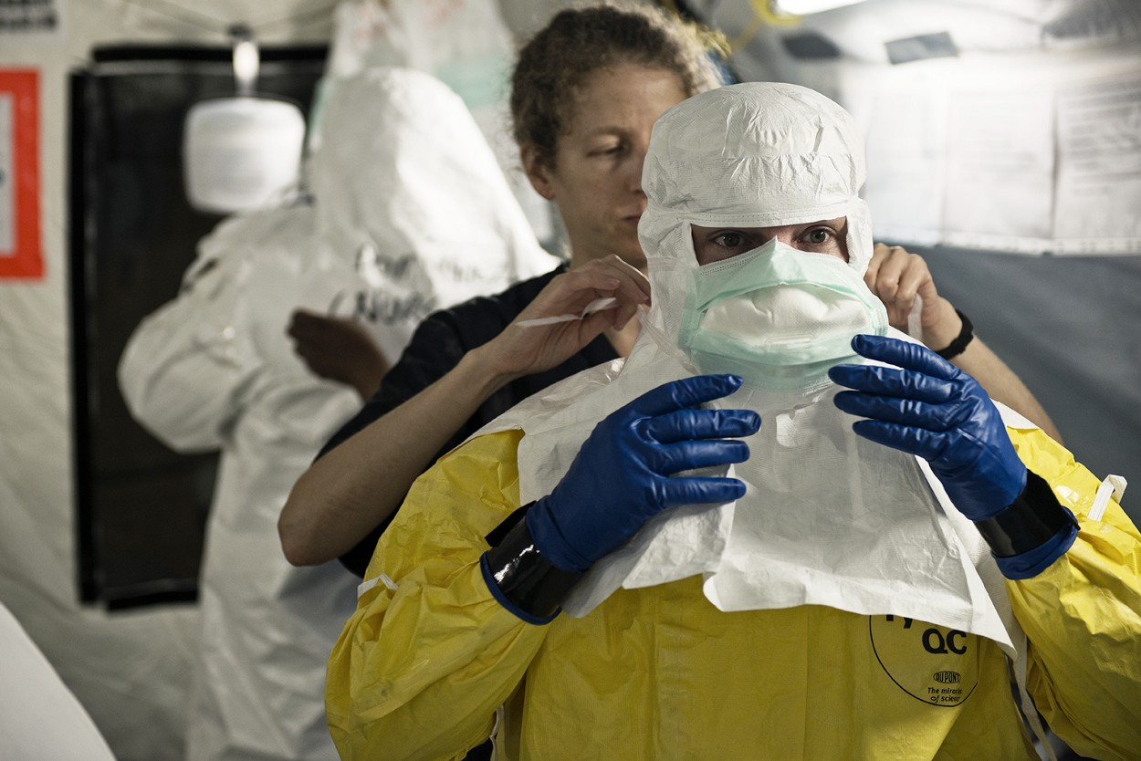 A surgical mask is being tied on a worker in a full yellow hazmat suit and gloves.
