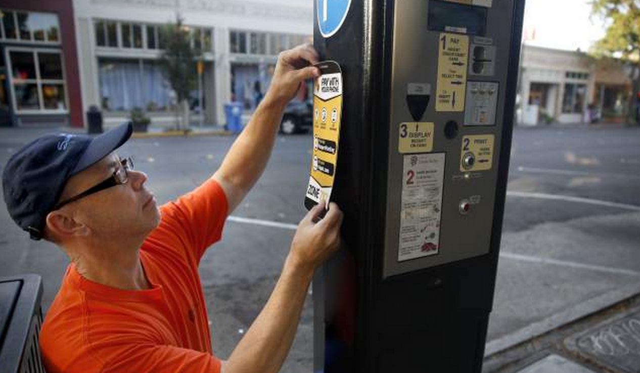 A Skilled Maintenance Worker Applying Decal Onto Paystation Photo From BETH SCHLANKER The Press Democrat