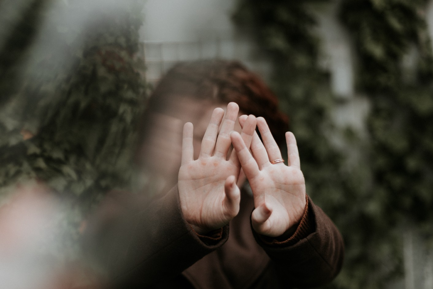 An image of a woman with her hands up, covering her face.