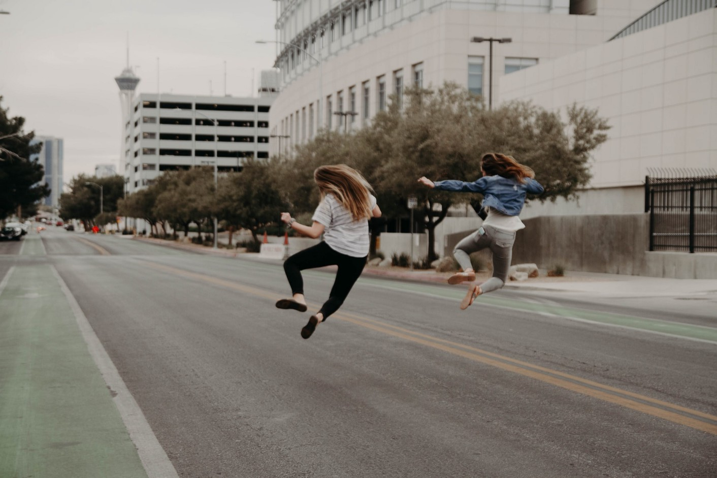An image of two girls jumping on a road.