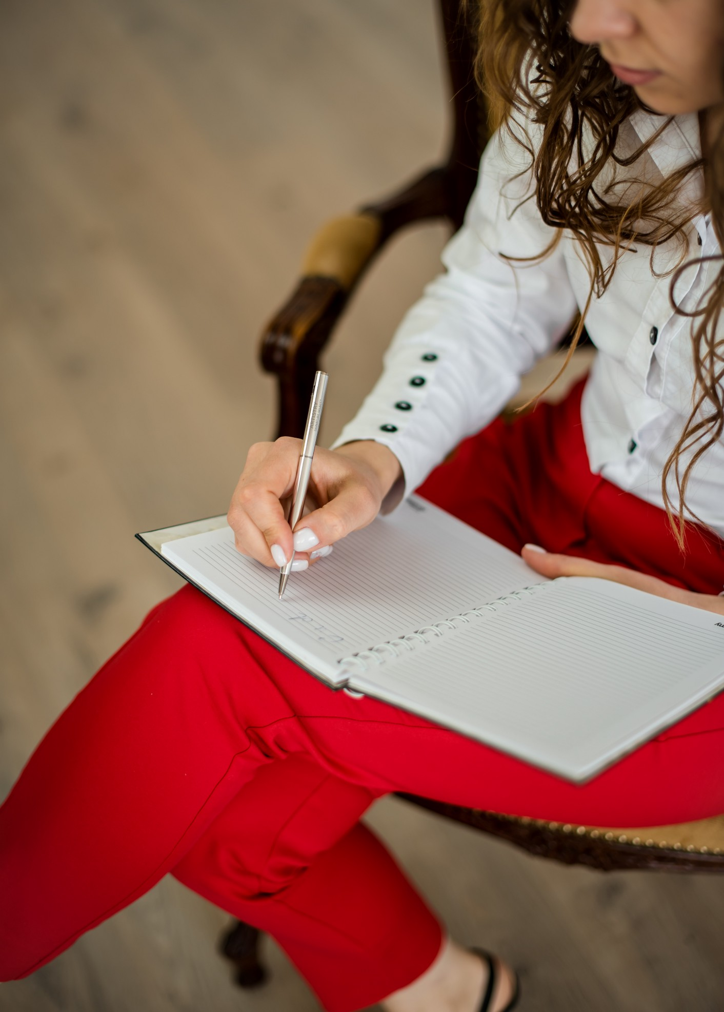 Image of a woman in red pants, writing in a notebook.