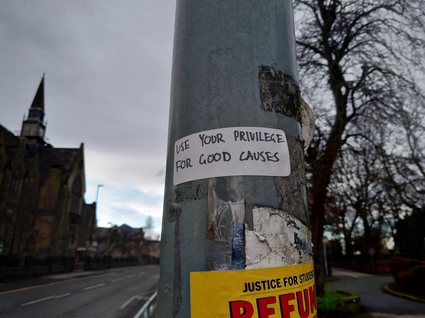 """Image of a pole with stickers on it, saying """"use your privilege for good causes""""."""
