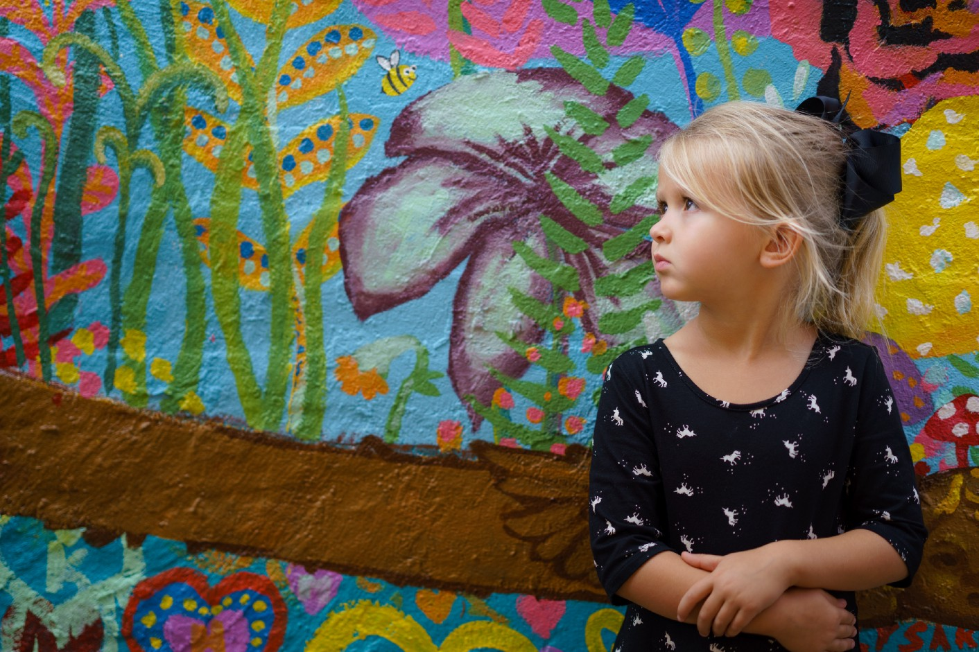 Image of a little girl in front of a floral wall.