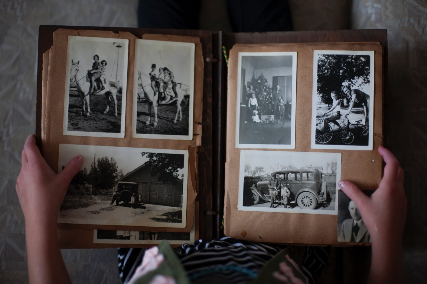 Image of hands holding an old photo album.