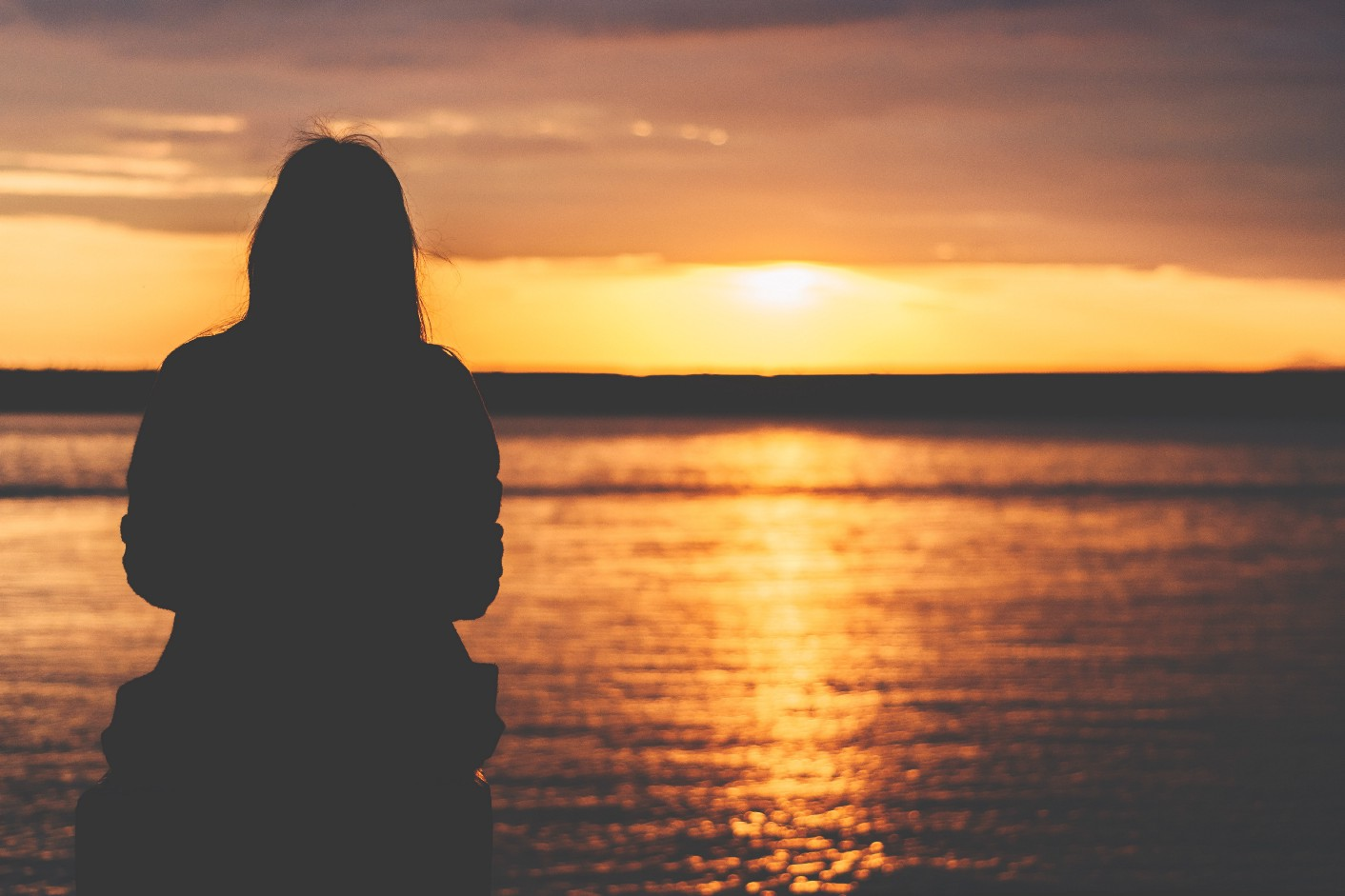 Image of silhouette looking at a sunset.
