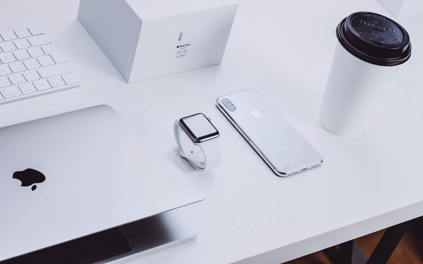A bunch of apple products in a very minimal setting, extremely white and clean looking