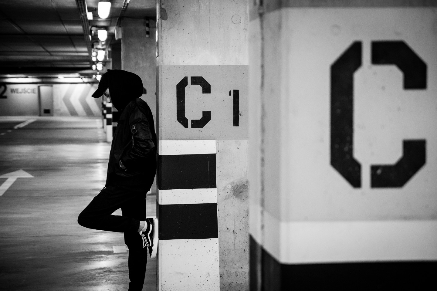 Man in black clothe and a hood leaning on a pillar in a parking garage with the letter C shown prominently