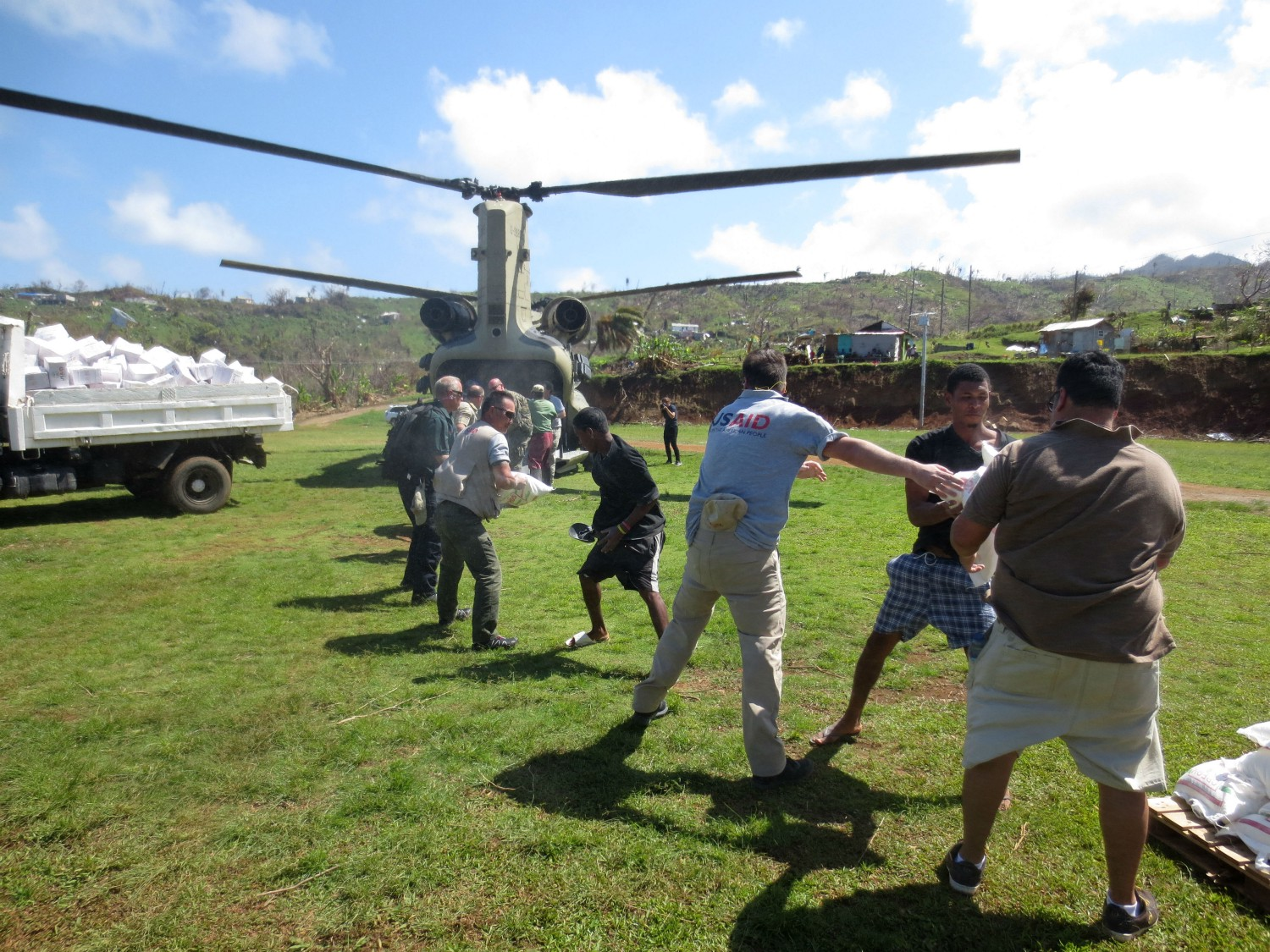 USAID staff work with local residents to unload emergency food assistance from the back of a U.S. military helicopter. Following Hurricane Maria, the U.S. military helped the Government of Dominica to transport relief supplies to hard-to-reach towns across the island. / Ricardo Herrera, USAID