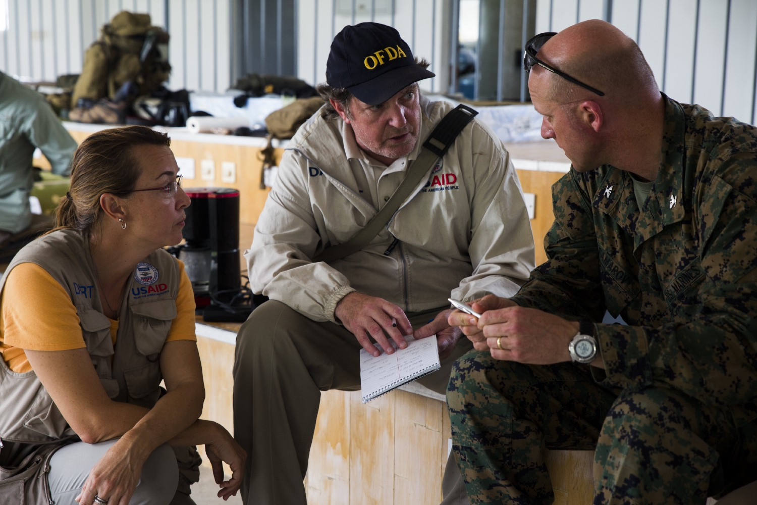 USAID DART Leader Tim Callaghan (center) discusses ongoing response efforts with U.S. Marine Col. Michael V. Samarov, commander of Joint Task Force — Leeward Islands (right), in Roseau, Dominica on Sept. 30, 2017. At the request of USAID, the U.S. military deployed aircraft and service members to assist in delivering relief supplies to Dominica in the aftermath of Hurricane Maria. Photo credit: Sgt. Melissa Martens, U.S. Marine Corps