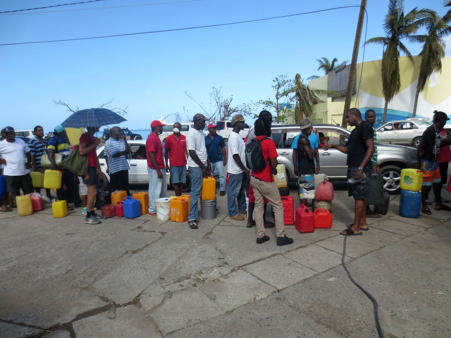 Dominicans standing in line for hours at a gas station to purchase fuel for cars and generators. / Julian Wyss, USAID