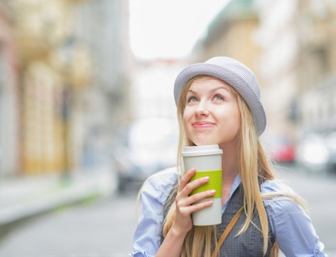 Thoughtful girl with cup of hot beverage on city street