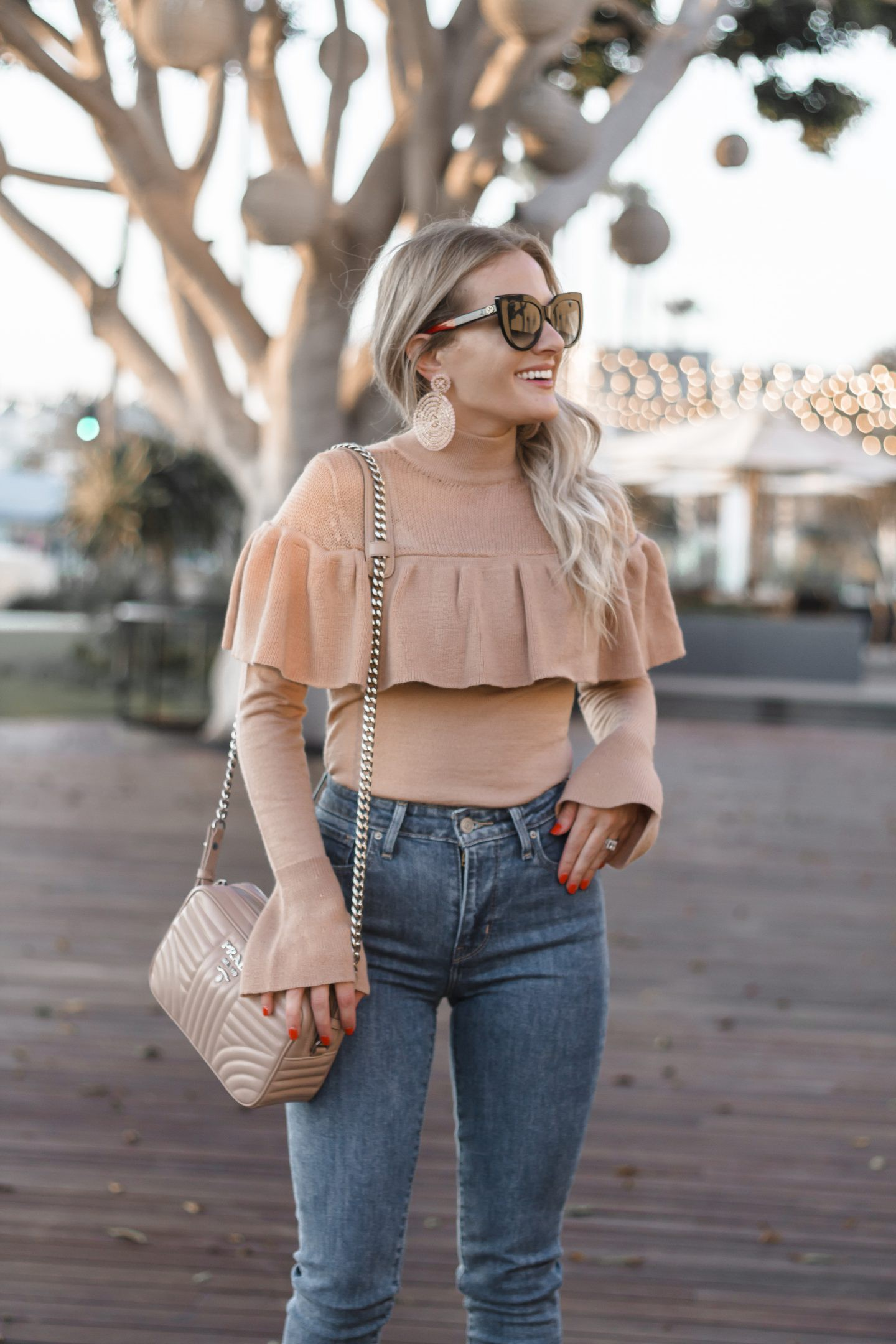 Statement Fall Sweater featured by top Orange County fashion blog, Dress Me Blonde: a blonde woman walking and wearing a Tularosa ruffle sweater, Levi's super skinny denim, Prada camera bag, BP open Toe Mules, disk champagne earrings