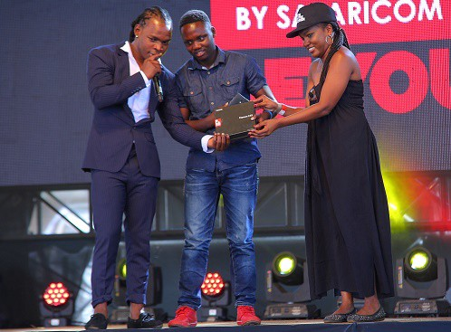 Safaricom's Yvonne Achieng awards Douglas Nyabuto, a Moi University student after winning the twitter contest. Timmy T-Dat looks on