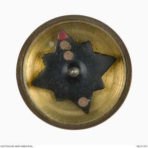 A tiny escape compass issued to Allied soldiers and airman. Australian War Memorial photo.