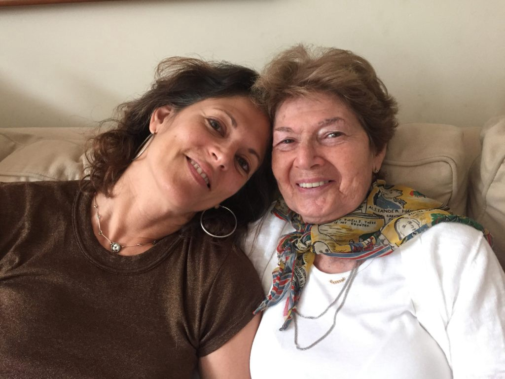 Mother and daughter still smiling despite: Alzheimer's parent sibling conflict.