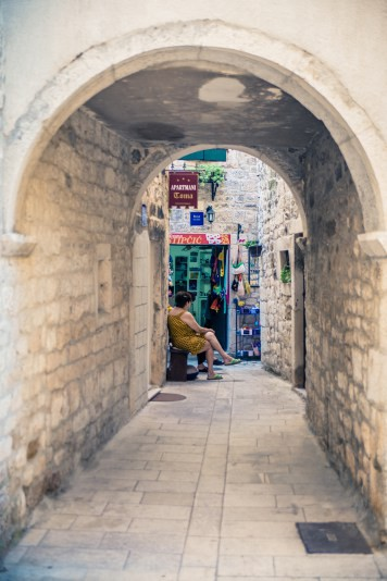Women chatting in front of a shop deep within the alleys of Trogir, Croatia