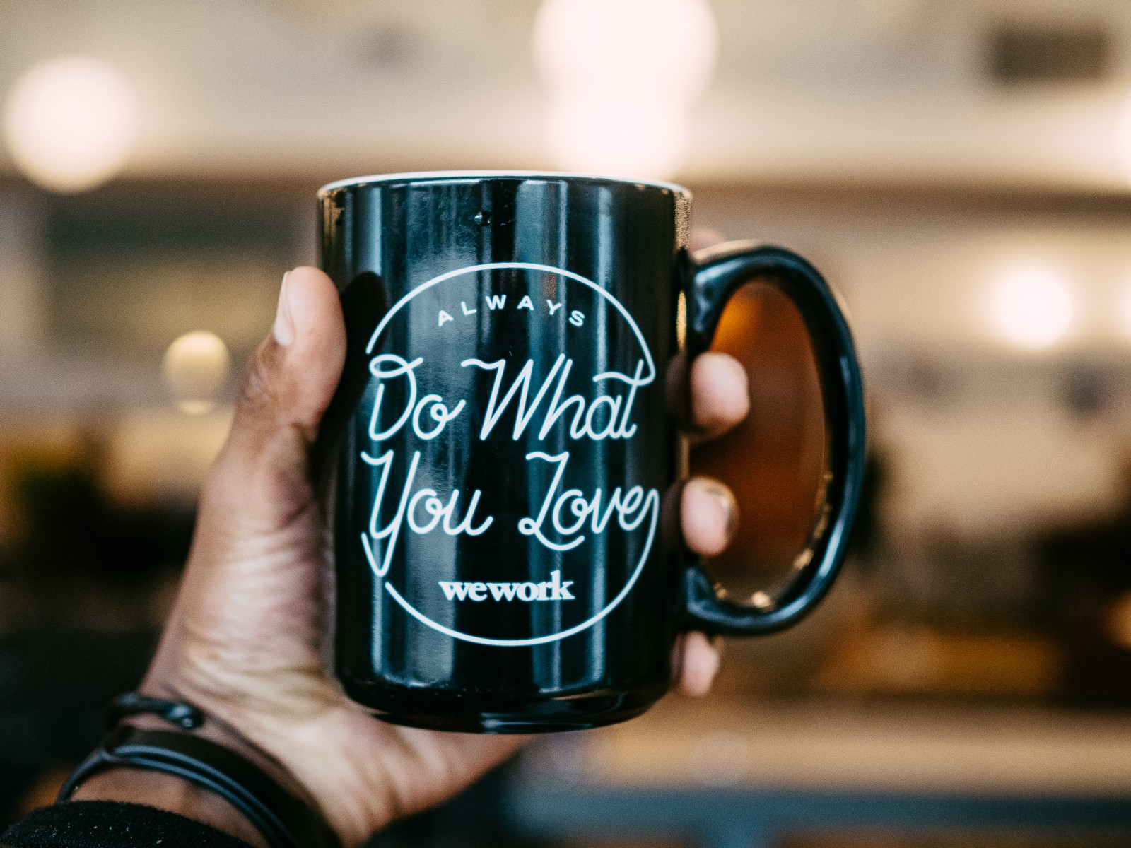 """Left hand holding a tea cup up at eye level. The cup reads """"always do what you love"""". This is about choosing your identity and working out what gives you energy. What fills you with love."""