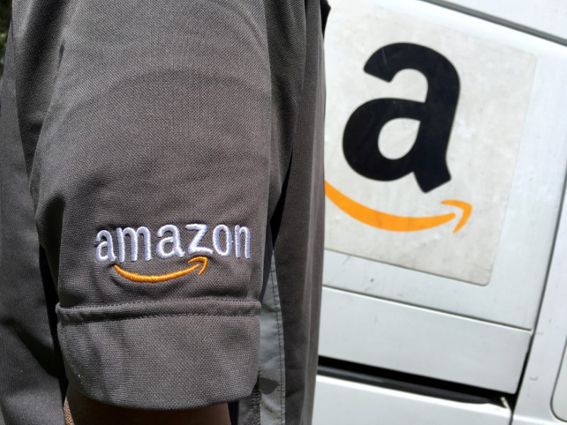 Amazon.com Inc driver stands next to an Amazon delivery truck in Los Angeles